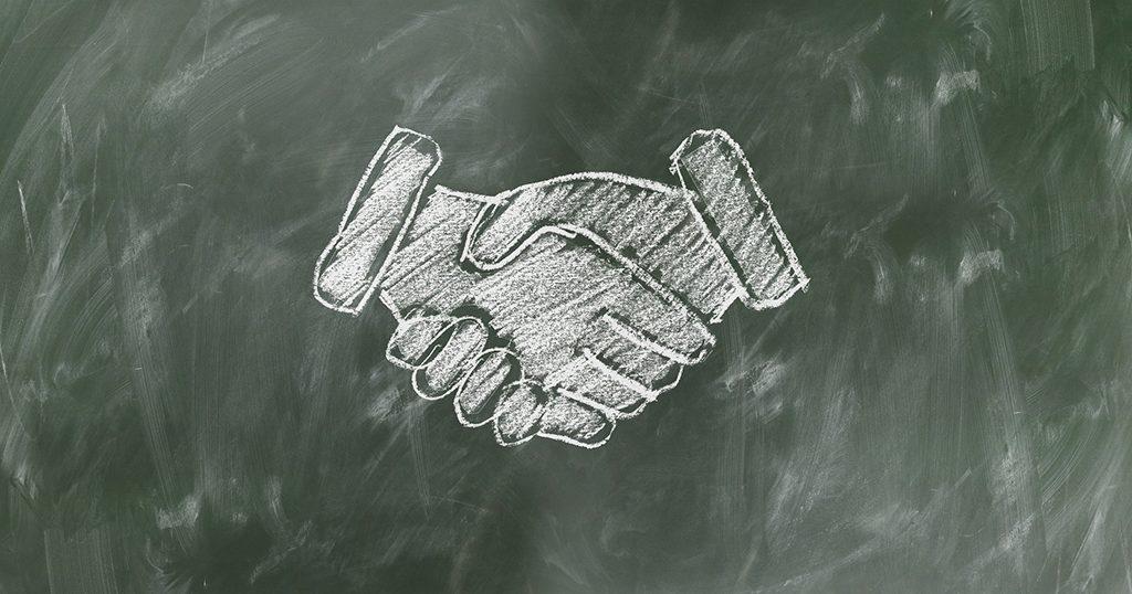 Kuva, jossa on liitutaululle piirretty valkoisella liidulla kättelevät kädet.