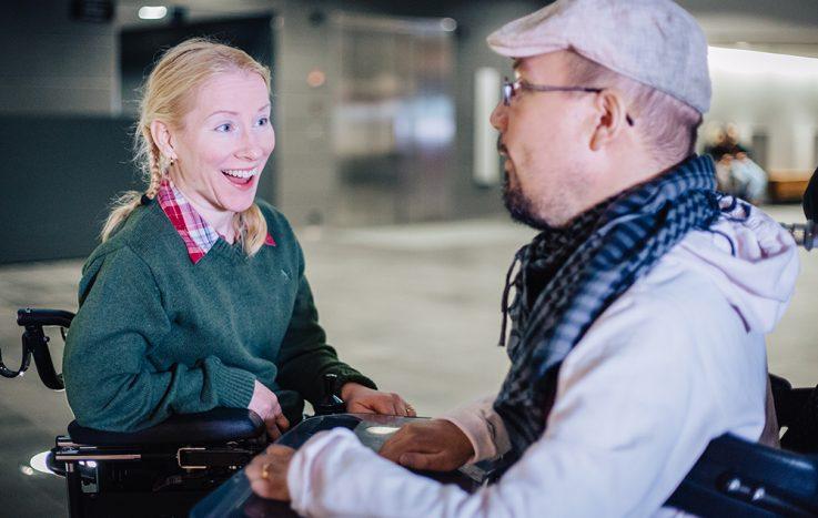 Kuvassa vasemmalla iloinen, nuori nainen, joka istuu pyörätuolissa. Kuvassa oikealla nuori mies, joka istuu pyörätuolissa.