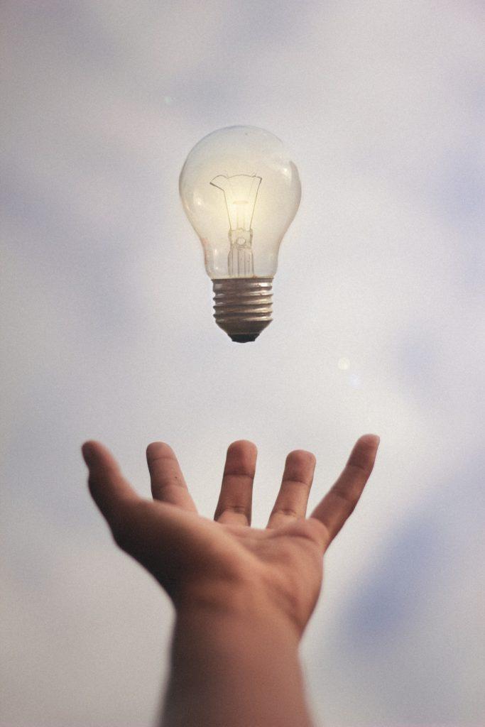 Kuvassa on käsi kämmen ylöspäin, käden päällä ilmassa on hehkulamppu.