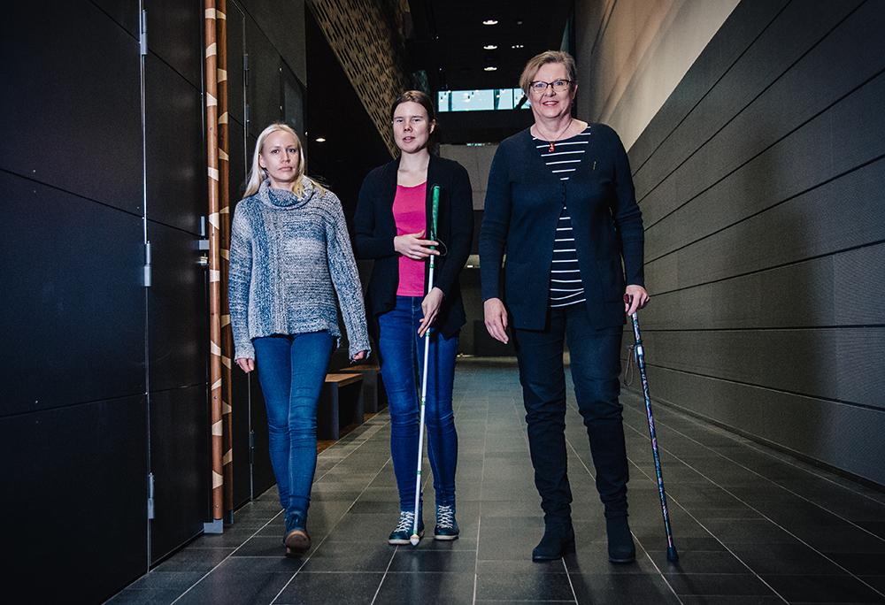 Kuvassa kolme naista kävelevät kohti kameraa. Vasemmalla on henkilökohtainen avustaja, keskellä näkövammainen, jolla on valkoinen keppi, ja oikealla nainen, jolla on kävelykeppi
