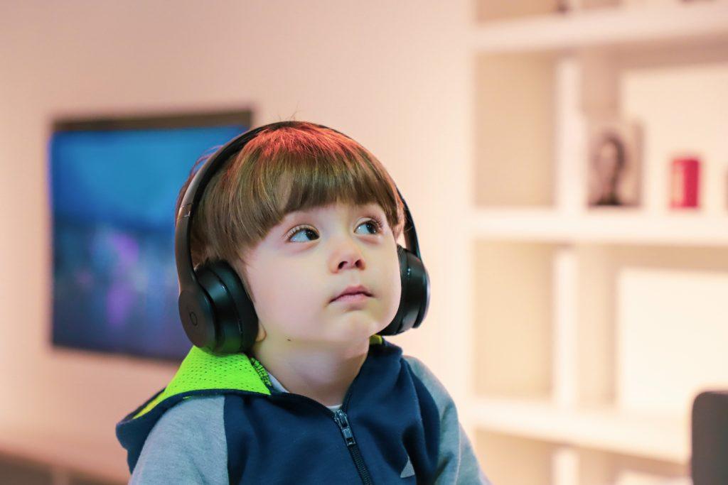 Kuvassa on pieni tummatukkainen poika, jolla on isot kuulokkeet korvilla. poika katselee yläviistoon mietteliäästi.