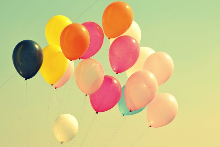 Erivärisiä ilmapalloja haalean väristä taivasta vasten.