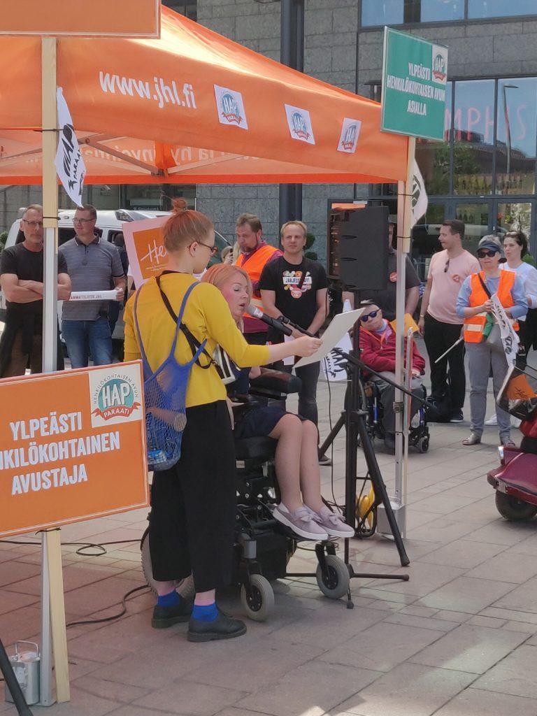 Kuvassa Hetan varapuheenjohtaja Elina Nieminen pitää puhetta Henkilökohtaisen avun paraatin alkutilaisuudessa. Hän on oranssin teltan edustalla, telttaa ympäröivät paraatin logot. Taustalla näkyy yleisöä.