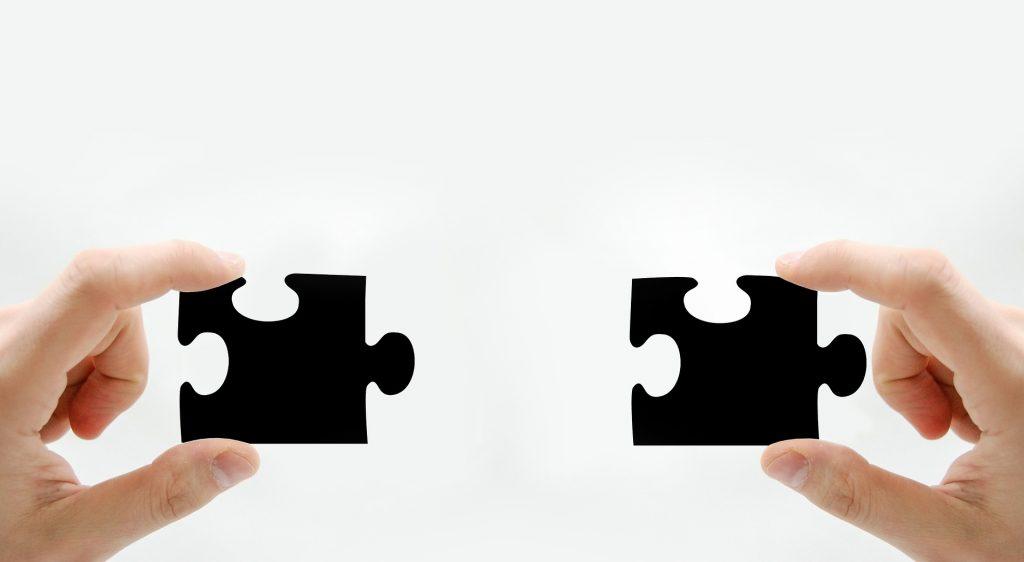 Kuvassa on kaksi kättä, joista kumpikin pitää mustaa palapelin palaa kädessään.