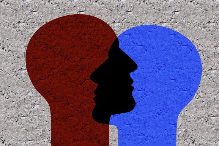 Kuvassa on harmaalla taustalla kahden ihmishahmon varjomaiset kuvat, jotka ovat osittain päällekkäin. Toinen on punainen, toinen sininen.