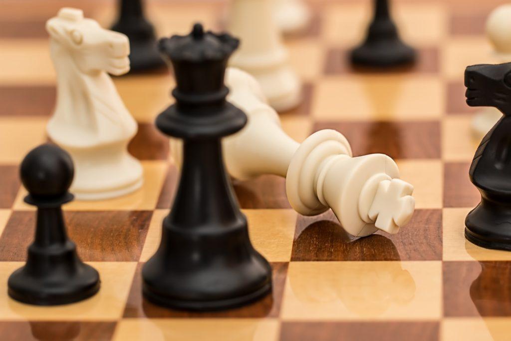 Lähikuva shakkipelistä, jossa valkoinen kuningatar on kaatuneena pelipöydällä.