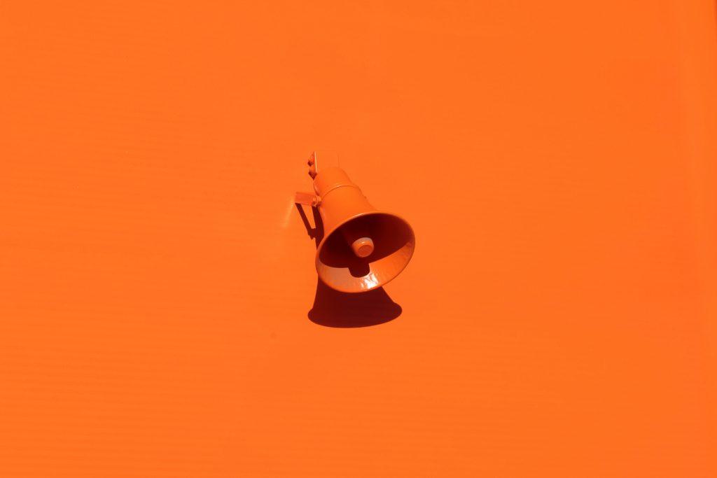 Kuvassa on oranssilla seinällä lähes saman värinen oranssi megafoni