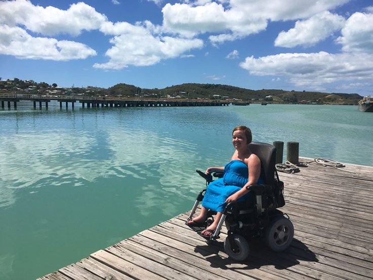 Kuvassa Palmuasema-blogin kirjoittaja Sanna Kalmari istuu sähköpyörätuolissa laiturilla turkoosin meren äärellä.