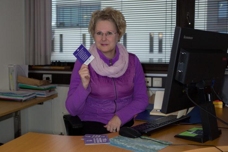 Kuvassa Pia Pulliainen istuu työpaikallaan työpöytänsä ääressä. Hän katsoo kameraan ja hänellä on kädessään pienikokoinen kirjanen YK:n vammaissopimuksesta.