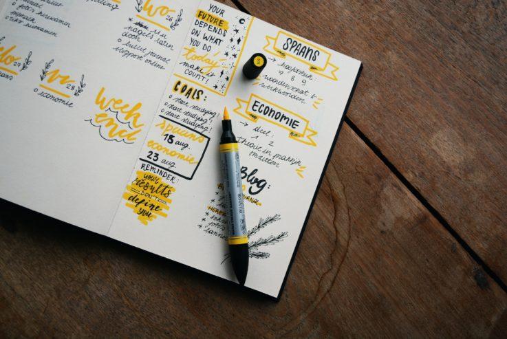 Kuvituskuva, jossa on ruskealla pöydällä avonainen muistivihko, johon on kirjoitettu koristeellisia muistiinpanoja keltaisella kynällä.