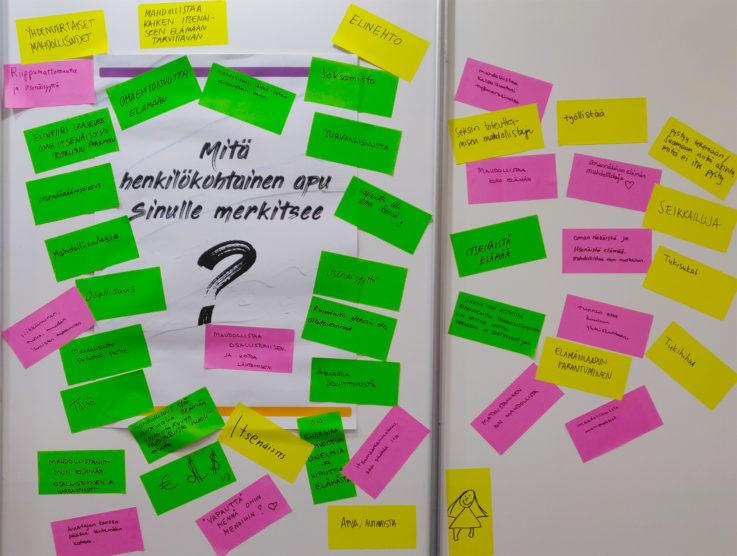 Kuvassa on Hetan messuosaston seinässä oleva juliste, jossa kysytään mitä henkilökohtainen apu sinulle merkitsee. Julisteen ympärillä on eri värisiä muistilappuja, joille messuvieraat ovat kirjoittaneet ajatuksiaan henkilökohtaisesta avusta. Kuva on sen verran kaukaa otettu, että muistilappuja ei kaikkia pysty lukemaan.