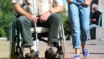 Kuvassa on vasemmalla mieshenkilö pyörätuolissa. Hänen vieressään käveelee farkkuihin pukeutunut nuori nainen.