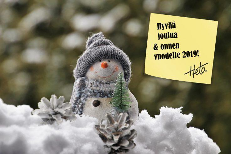 Kuvassa on hymyilevä lumiukkokoriste-esine, jolla on harmaa pipo ja kaulahuivi. Kuvan oikeassa yläkulmassa on keltainen muistilappu, jossa lukee hyvää joulua ja onnea vuodelle 2019.