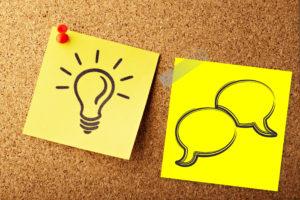 Kuvituskuva, jossa on muistitaululla kaksi keltaista post it -lappua: toisessa on piirretty hehkulamppu ja toisessa kaksi puhekuplaa.