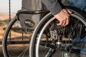 Kuvassa on lähikuvassa pyörätuolissa oleva mieshenkilö. Kuvassa näkyy vain pyörätuolin takaosa, rengas ja rengaasta kiinnipitävä käsi.