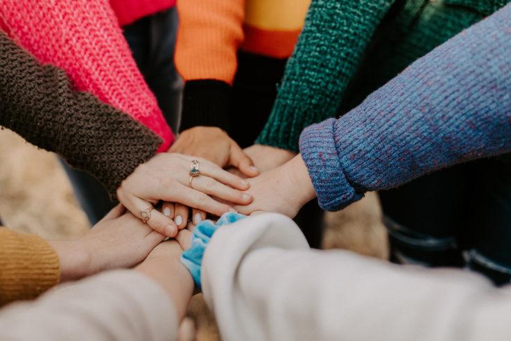 Kuvassa näkyy ympyrämuodostelmassa olevien ihmisten kädet, jotka ympyrän keskellä koskettavat toisiaan.