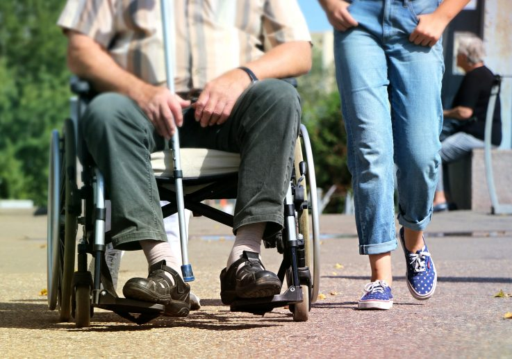Kuvassa on vaseammalla pyörätuolissa oleva mieshenkilö. Hänen vieressään kävelee farkkuihin pukeutunut henkilö. Heidän on kuvattu noin vyötäröstä alaspäin.