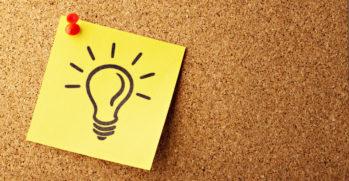 Kuvituskuva, jossa on ilmoitustaululle laitettu keltainen muistilappu, jossa on piirretty hehkulampun kuva.