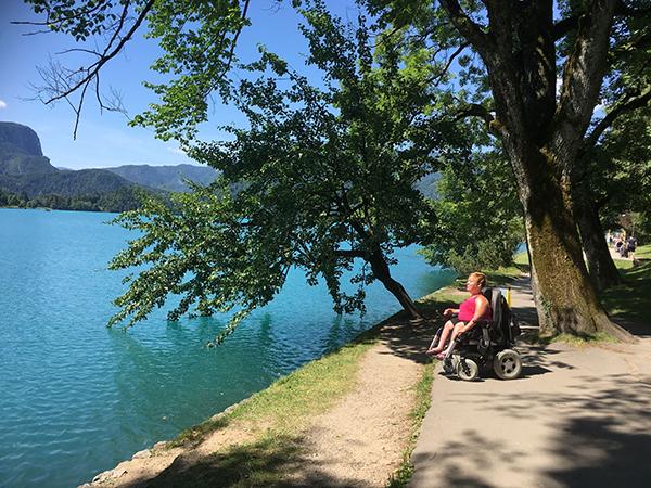 Kuvassa Palmuasema-blogin pitäjä Sanna Kalmari istuu sähköpyörätuolissa turkoosin meren rannalla, puun varjossa, ja katsoo merellepäin. Aurinko paistaa.