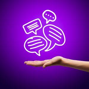 Kuvassa on violetti tausta, jossa on ihmisen käsi, jonka yläpuolella on piirrettyjä puhekuplia